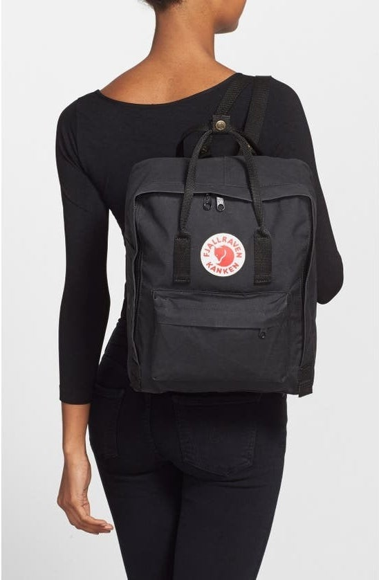 The square-shaped backpack with a zipper all the way around the front, front pocket, and short straps on the top over one shoulder on a model's back