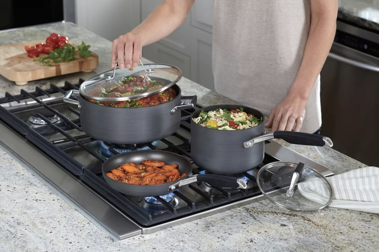 Person is cooking multiple foods in various pots and pans on a stove