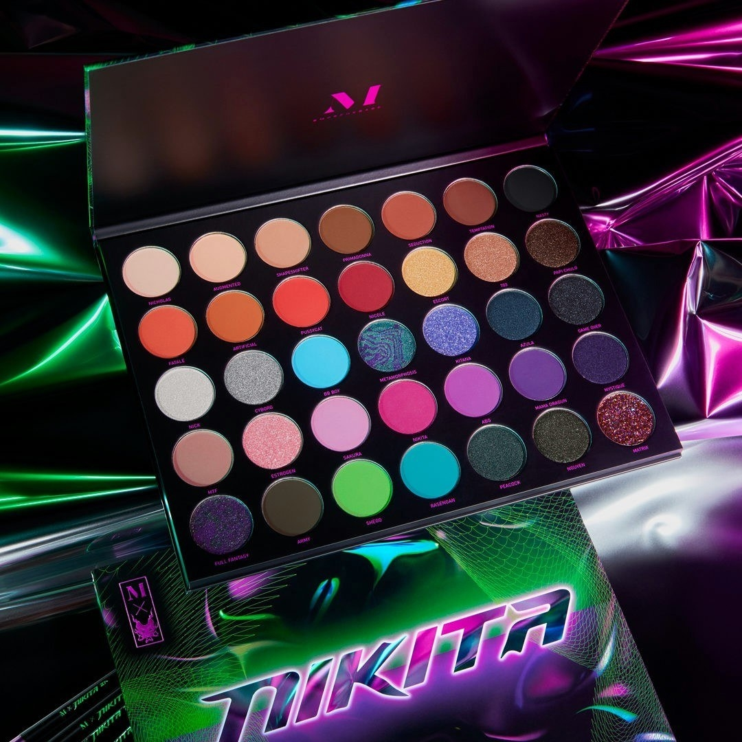 An open palette showing all the shades of the eyeshadows against a neon-noir backdrop
