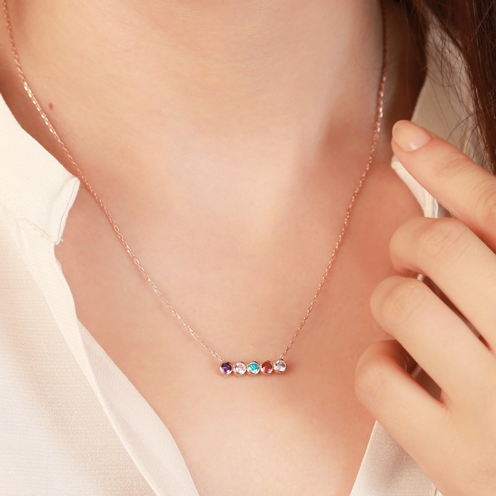 close up of necklace on neck with five birthstones