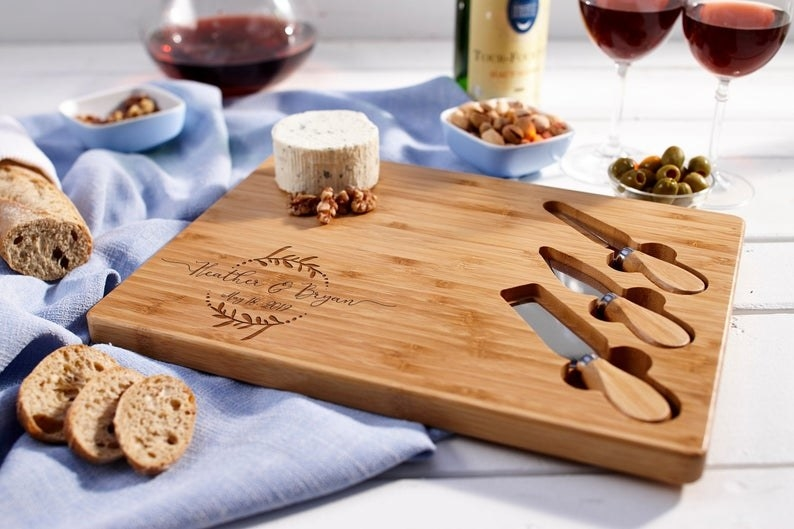cheese board with bread, cheese, wine, and three knives