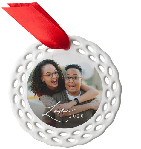 a circular ceramic ornament with tiny oval cut outs around it and a photo of a couple int he middle