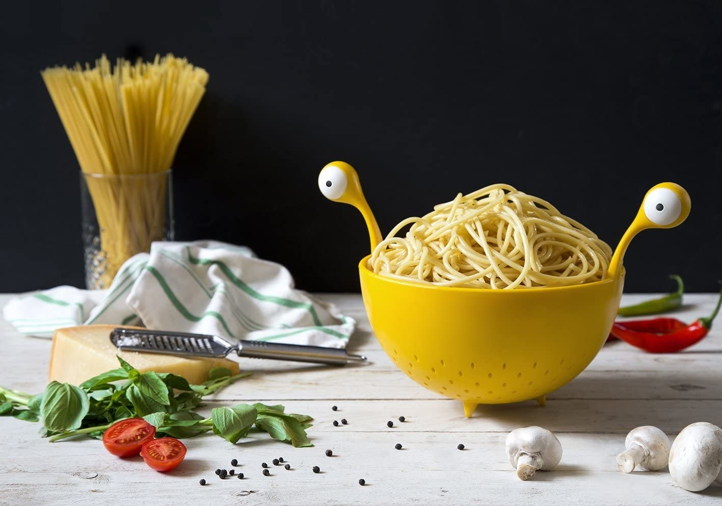 A spaghetti monster strainer full of noodles on table next to various herbs and vegetables and a block of cheese