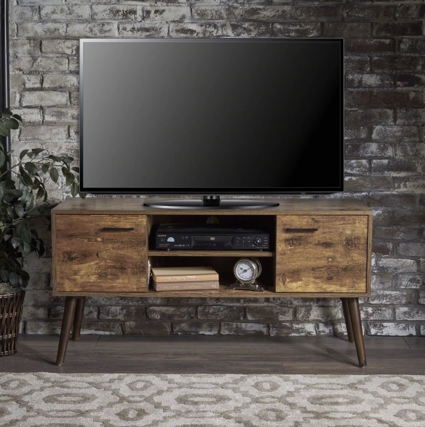 The dark wood entertainment center with a TV on top in a living space