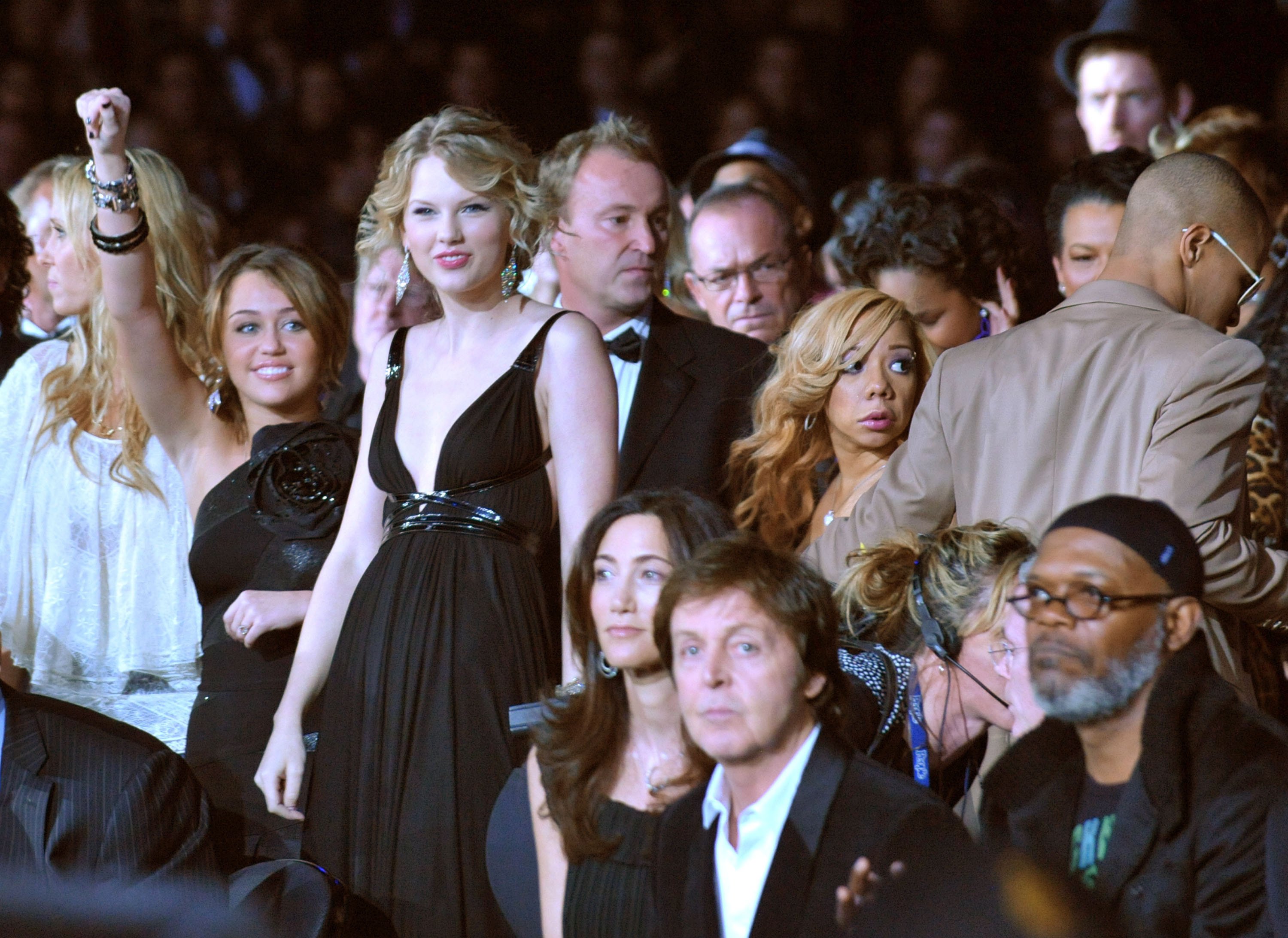 Miley Cyrus with a smile and her arm raised as she stands near Taylor Swift, Tiny, T.I., Paul McCartney, and Samuel L Jackson at an event
