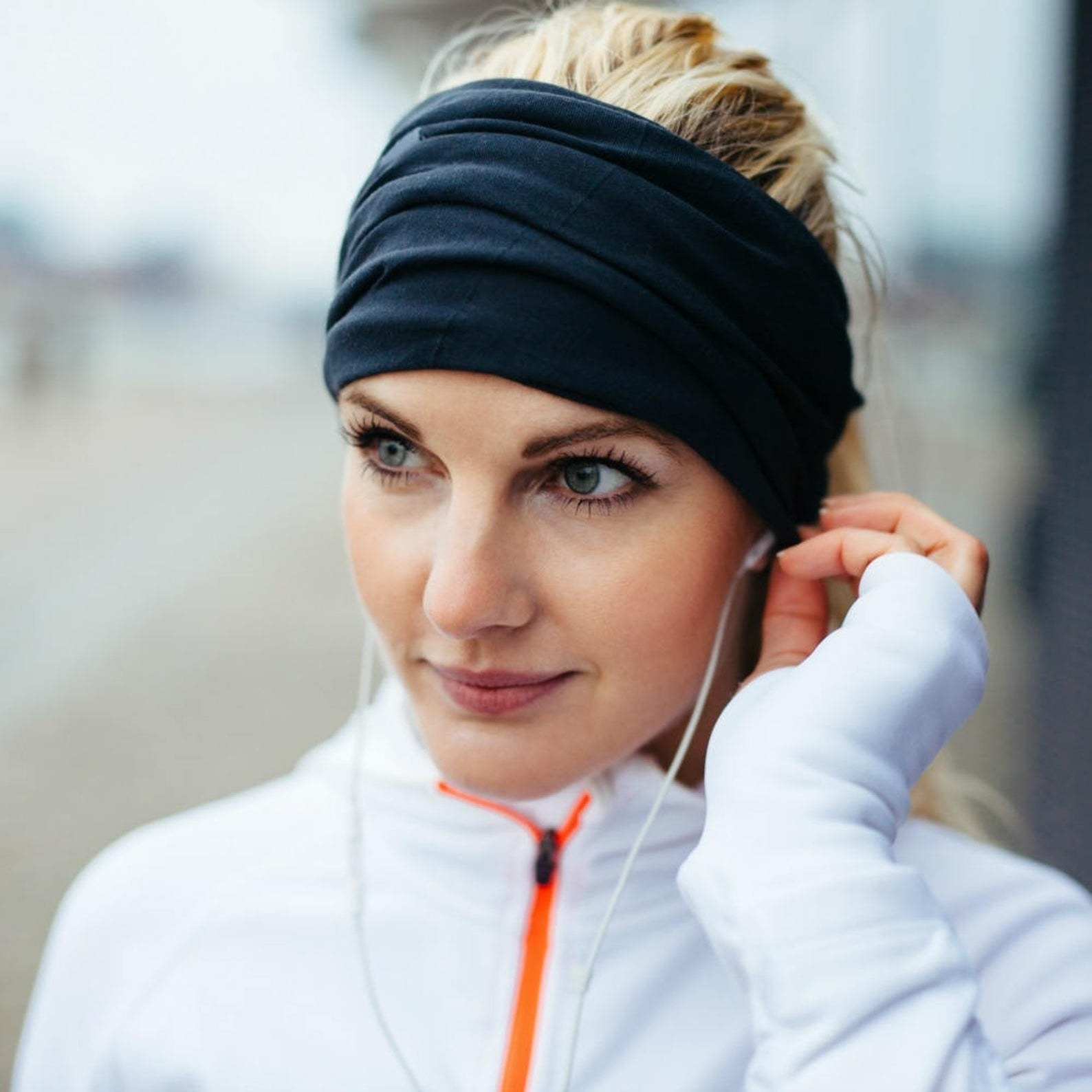 woman with headband on putting an earphone in her ear