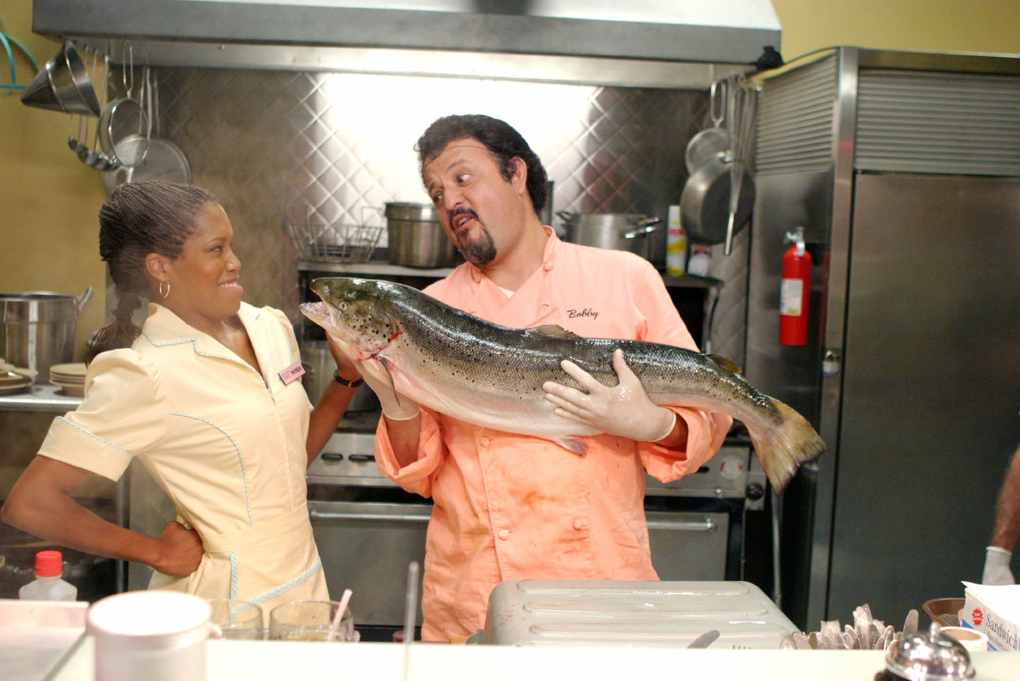 Bobby putting a big fish near Rhonda's face in the kitchen of the diner
