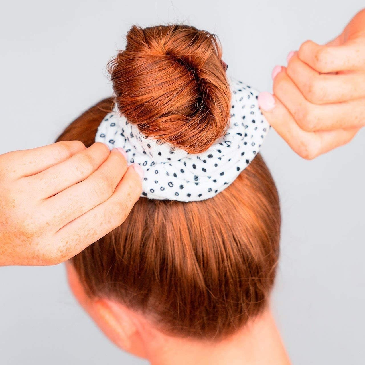 A rear view of a person wearing their hair in a bun, secured by the terrycloth scrunchie