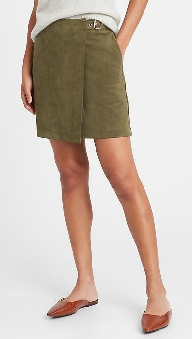 model wearing a green suede wrap mini skirt