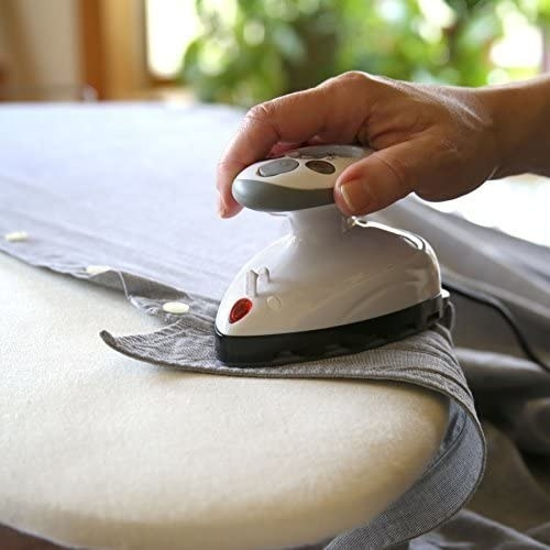 A person using the mini iron to smooth out their shirt collar