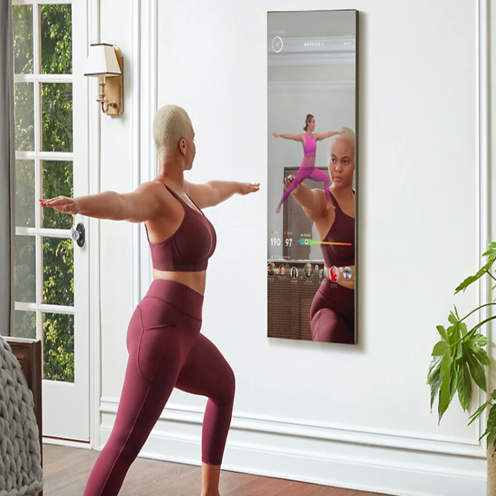A person doing yoga in front of the mirror.