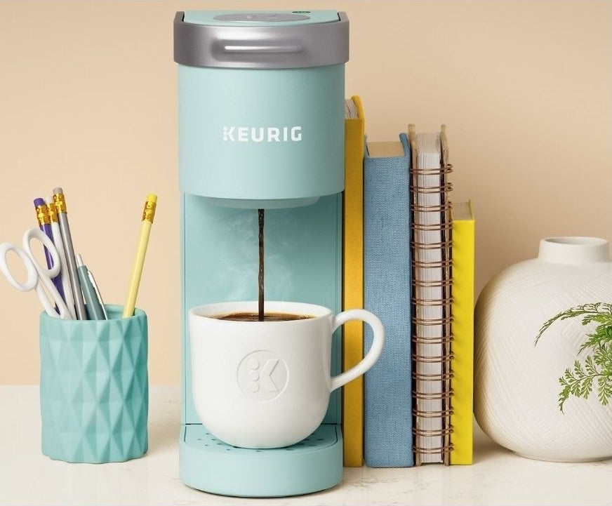 keurig k-mni single serve coffee maker sits on a decorated desk pouring coffee into a mug