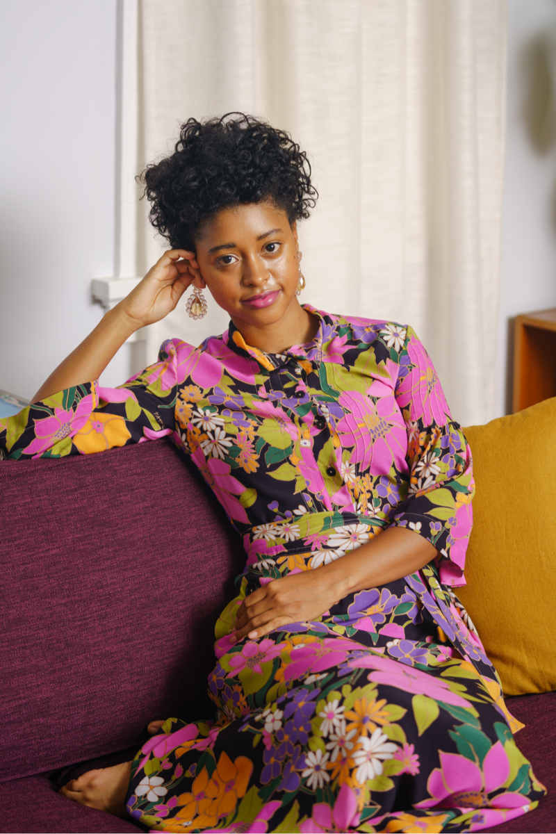 A model wearing a floral dresses lounges on a couch