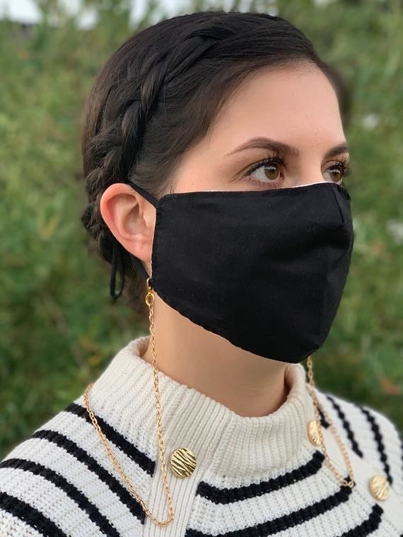 Model wears black face mask with thin gold face mask chain