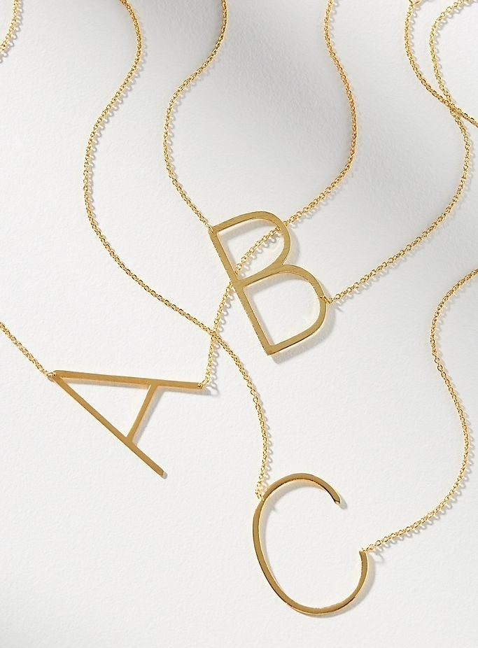 The gold oversized initial necklaces in A, B, and C