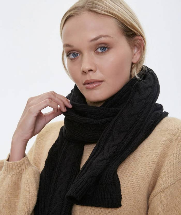 Model is wearing a black knit scarf around neck with a cream sweater