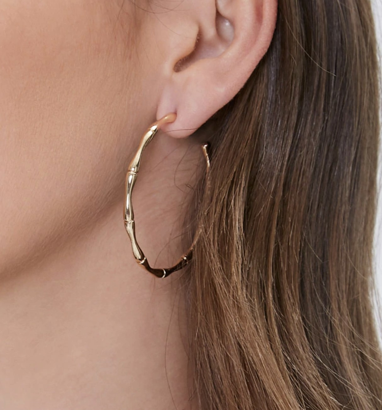 Model is wearing gold hoop earrings