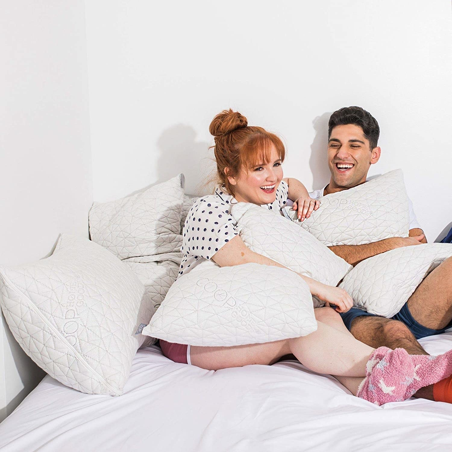 Two models sit on a bed covered in coop home good memory foam pillows