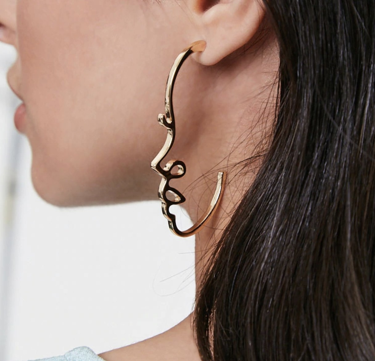 Model is wearing gold earrings shaped like a side profile of a face