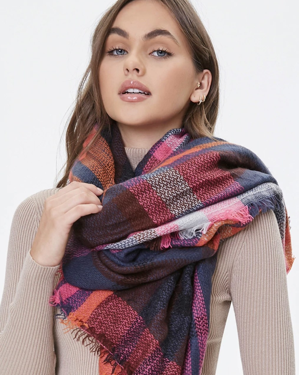 Model is wearing a plaid infinity scarf over a mauve turtleneck sweater