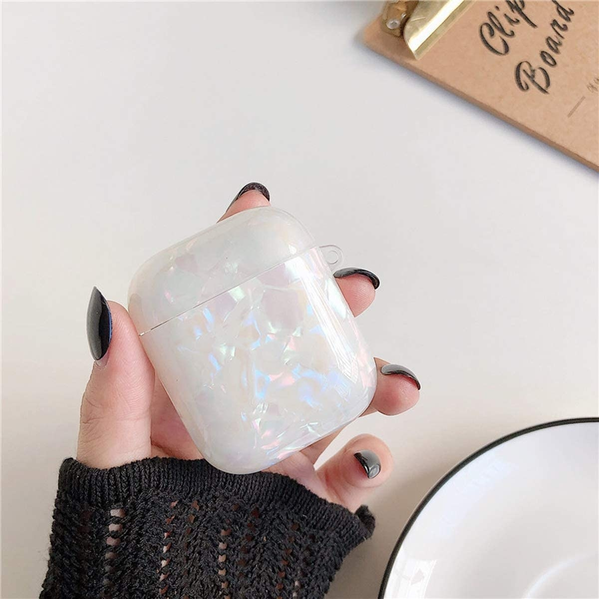 Model holding white iridescent AirPods case