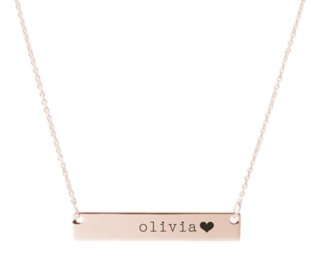 a rose gold necklace with a bar charm with the name olivia and a heart