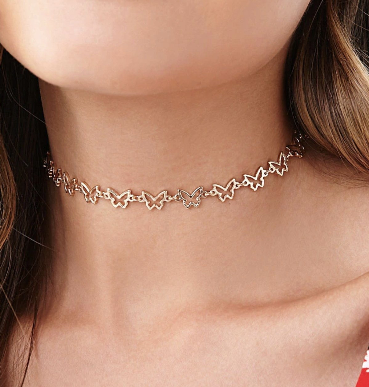 Model is wearing a gold choker necklace with a repeated butterfly pattern