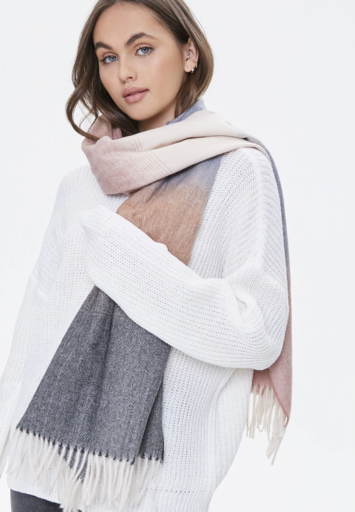 Model is wearing an ombre scarf in the colors grey, peach, and pink over a white sweater