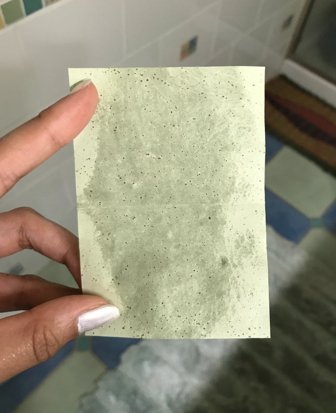 reviewer image of blotting sheet showing tons of oil that was removed from forehead