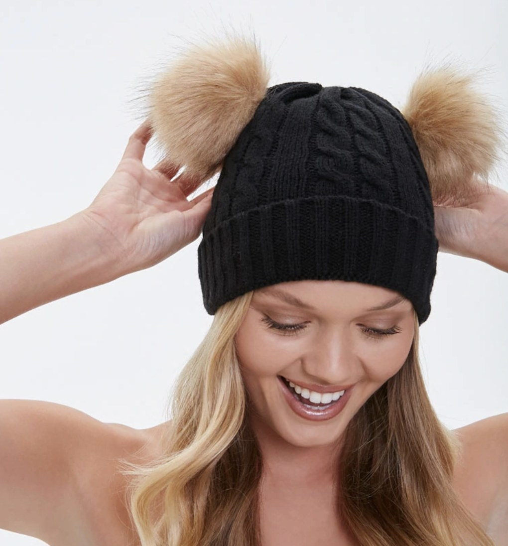 Model is wearing a black beanie with two pom poms on top