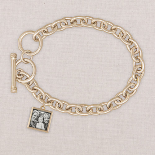 a gold charm bracelet with a picture in a square charm