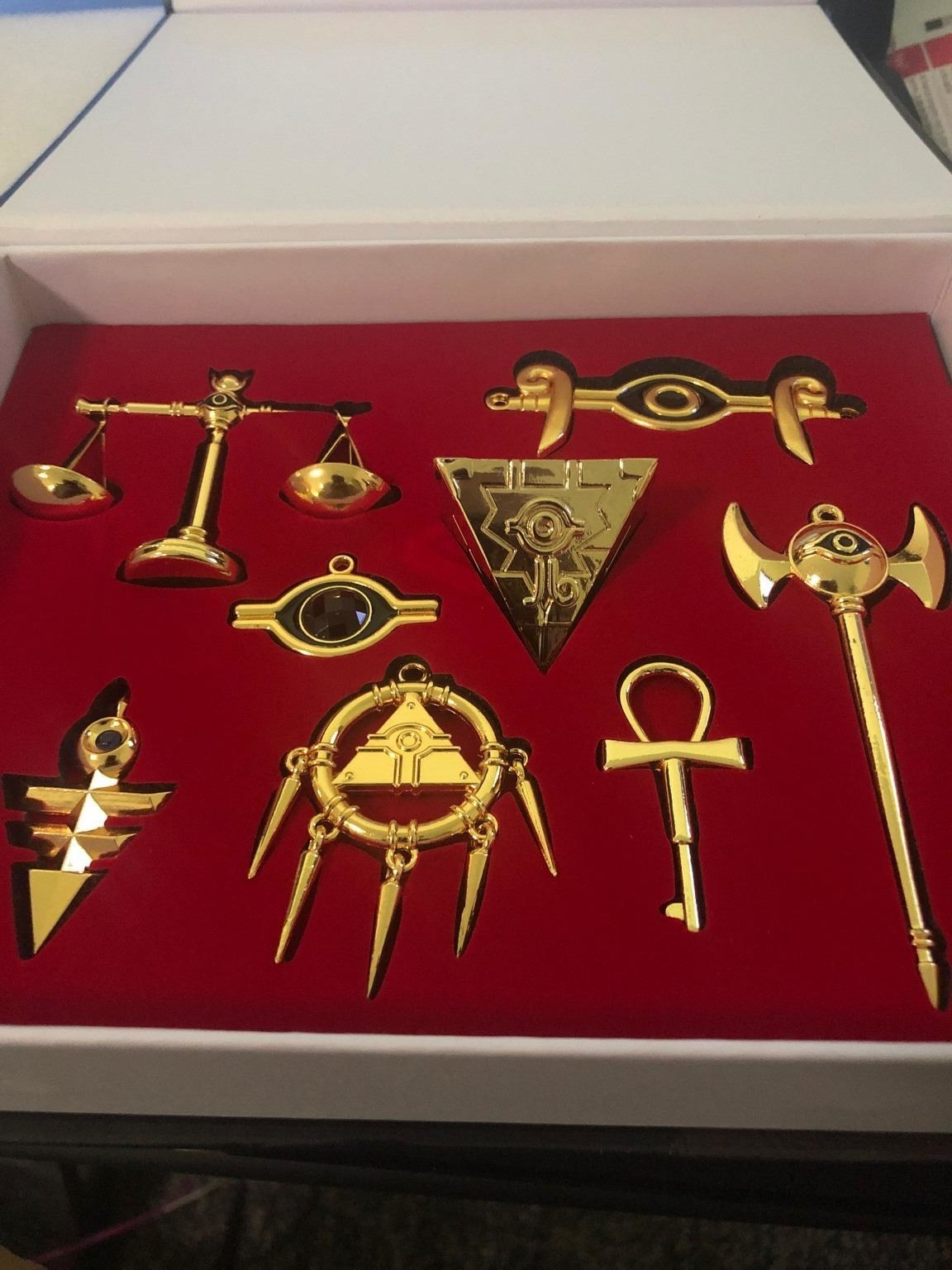 A reviewer's photo of the small gold item replicas in a red-lined gift box