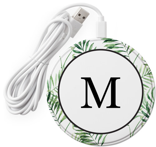 a round wireless charger with palm leaves around the edges and an M in the middle