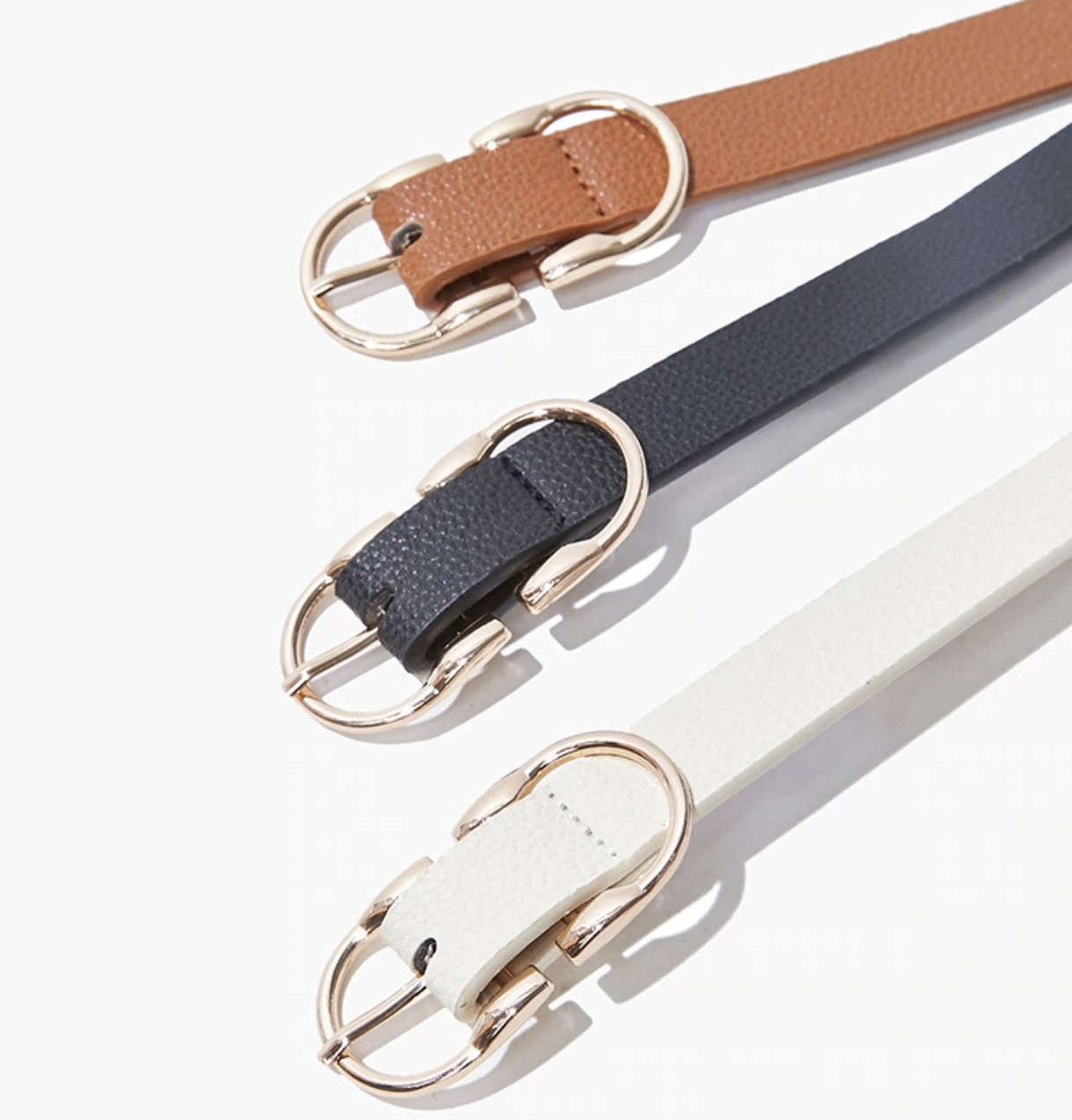 A black, tan, and white textured belt set