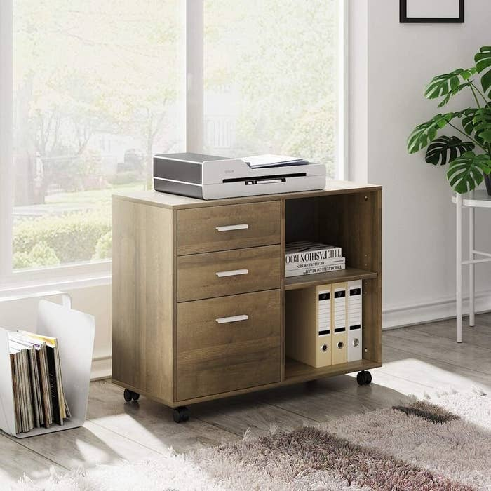 The wooden, rolling filing cabinet with three drawers and two shelves