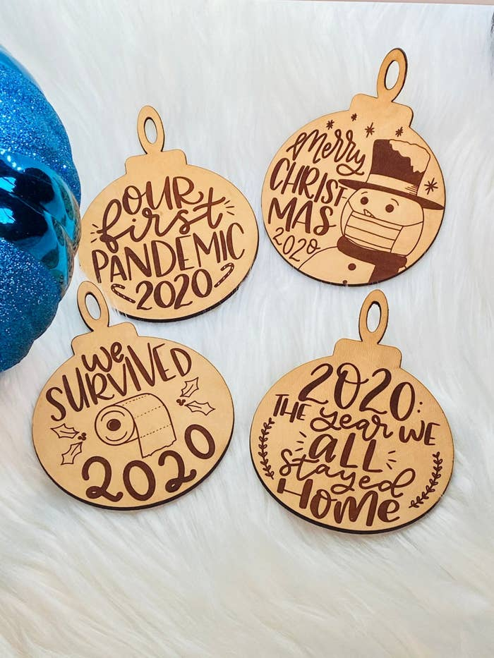 four ornaments that say our first pandemic 2020, merry christmas 2020 with a snowman with a mask on, we survived 2020 with a toilet paper roll, and 2020 the year we all stayed home