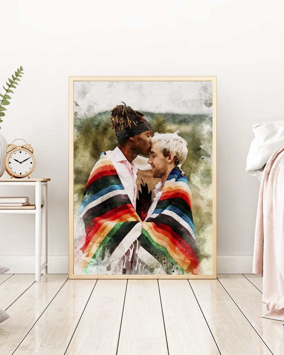 A couple wrapped in a blanket, one kissing the other's forehead, in a watercolor print