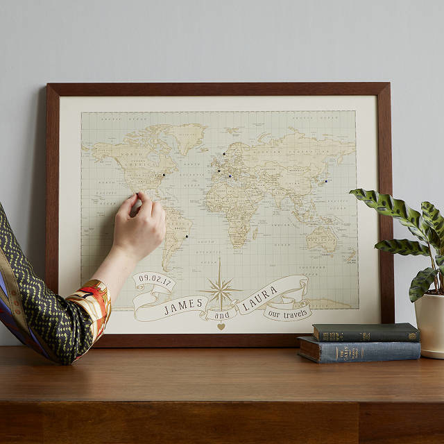 Personalized anniversary banner underneath vintage-style world map with push pins where people have traveled