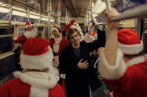 Dash on the subway surrounded by Santas