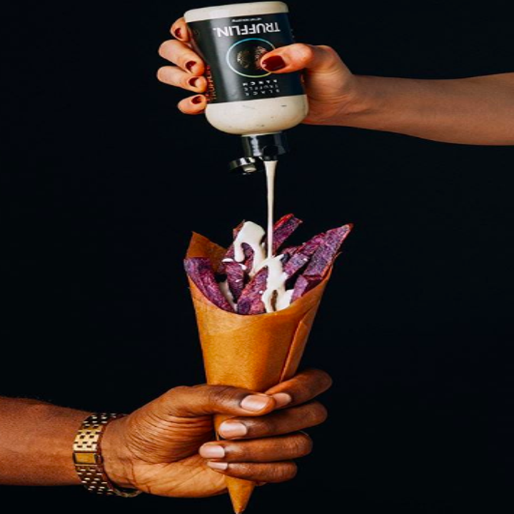 Person holding cone of food with another person putting sauce on top