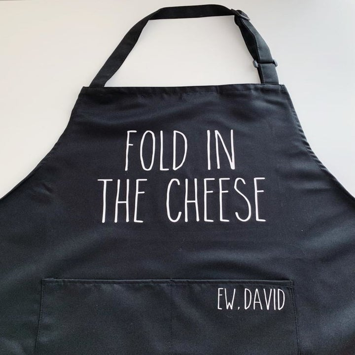 "The apron with ""Ew, David"" written on one of the large front pockets"
