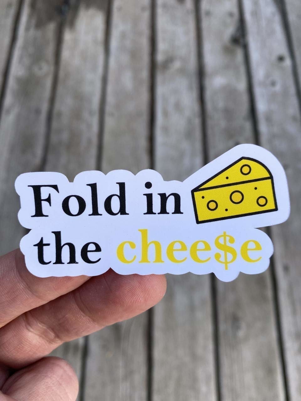 "The sticker that reads ""Fold in the cheese"" with a drawing of cheese"