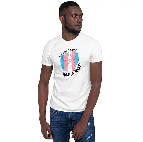 "a model wearing the T-shirt with a blue, pink, and white fist surrounded by the words ""the first pride was a riot"""