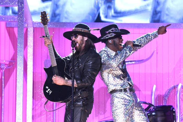 Billie Ray Cyrus perform the song wearing flashy suits and cowboy hats on the Grammy Awards