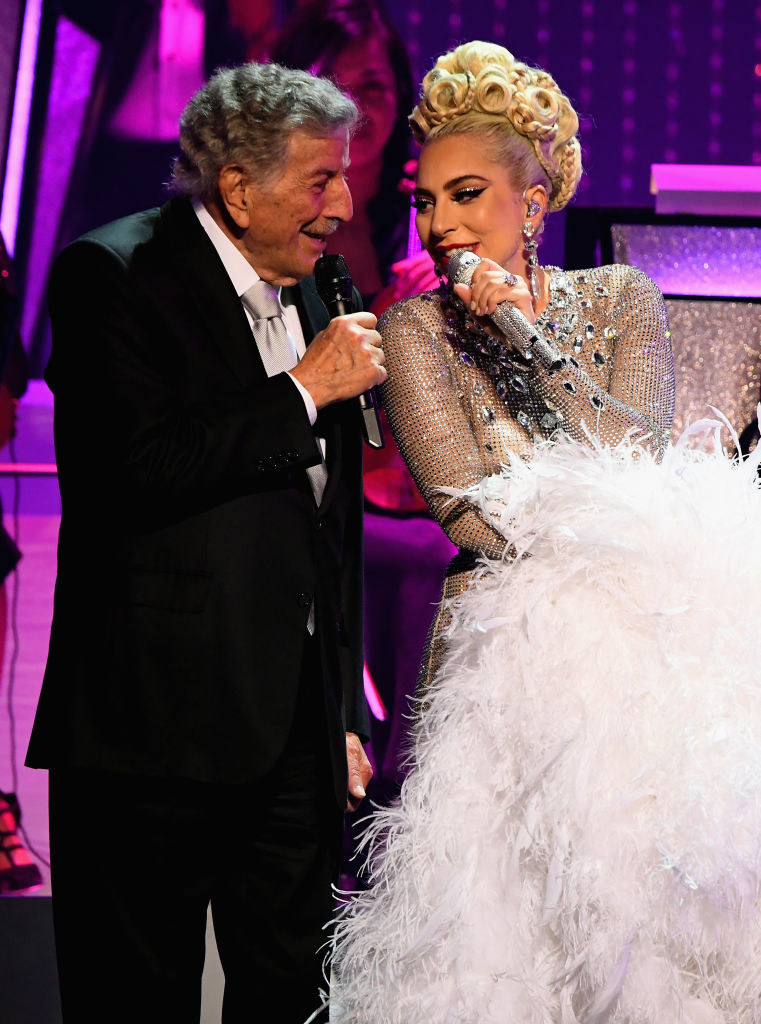 Tony Bennett wears a sharp suit and Lady Gaga wears a beautiful dress as they sing close together