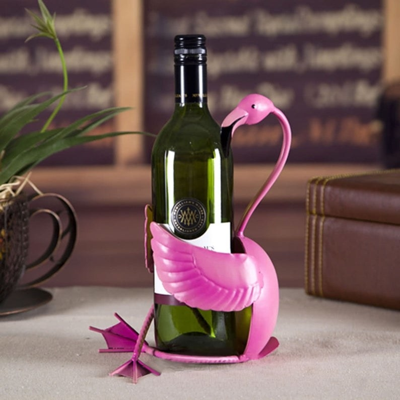 A flamingo holds a bottle of wine
