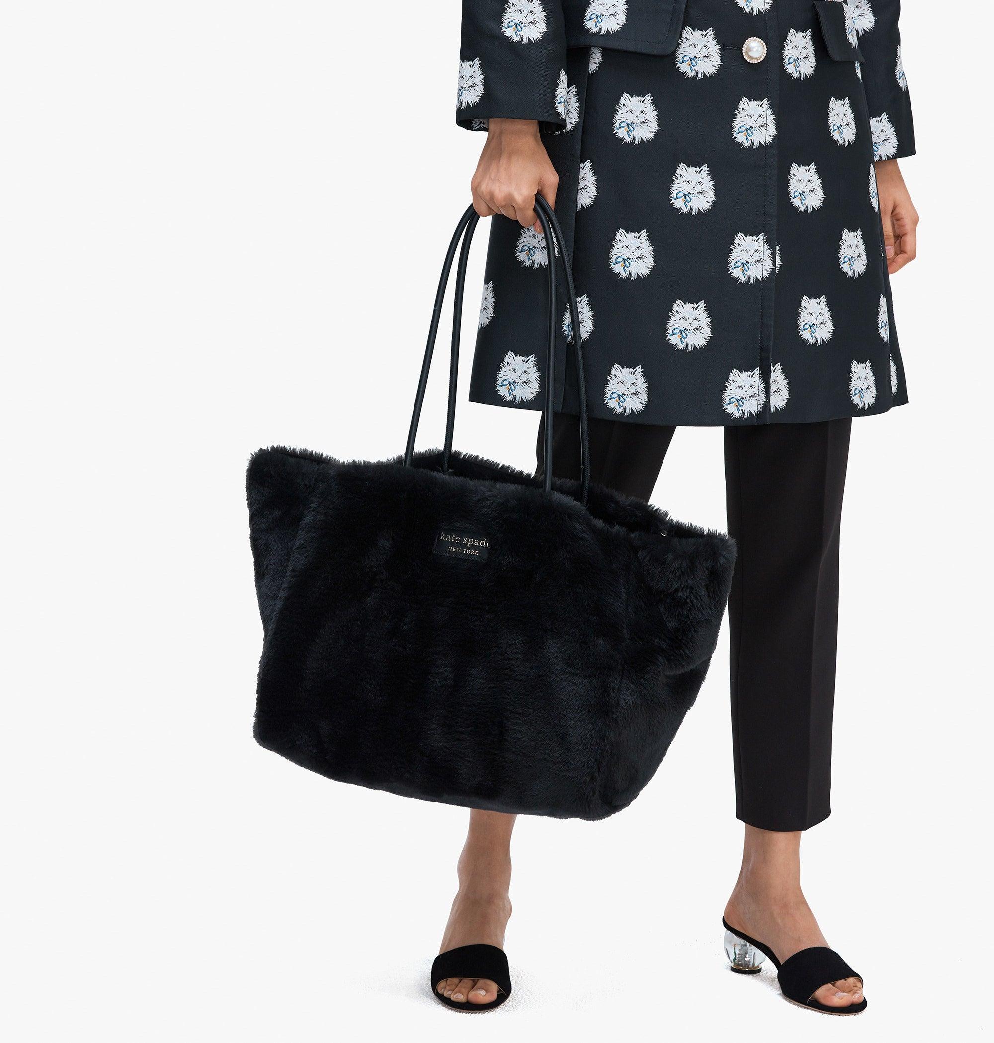 Model holding the black faux fur bag