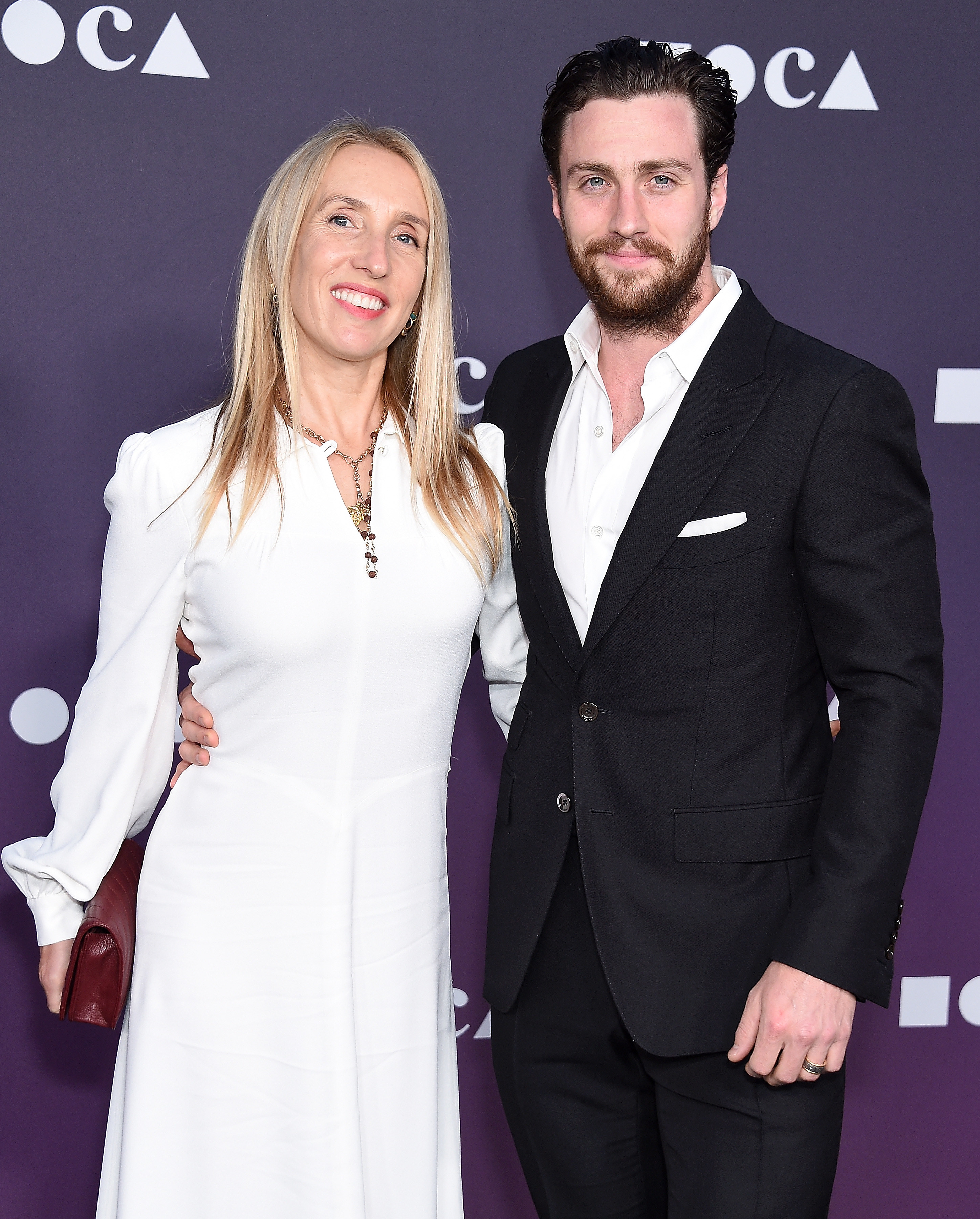 Sam Taylor-Johnson and Aaron Taylor-Johnson smile arm in arm at a film premiere