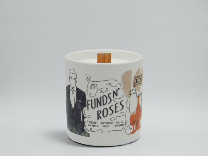 The white candle in a ceramic cup illustrated with themed doodles, including a silhouette of Johnny