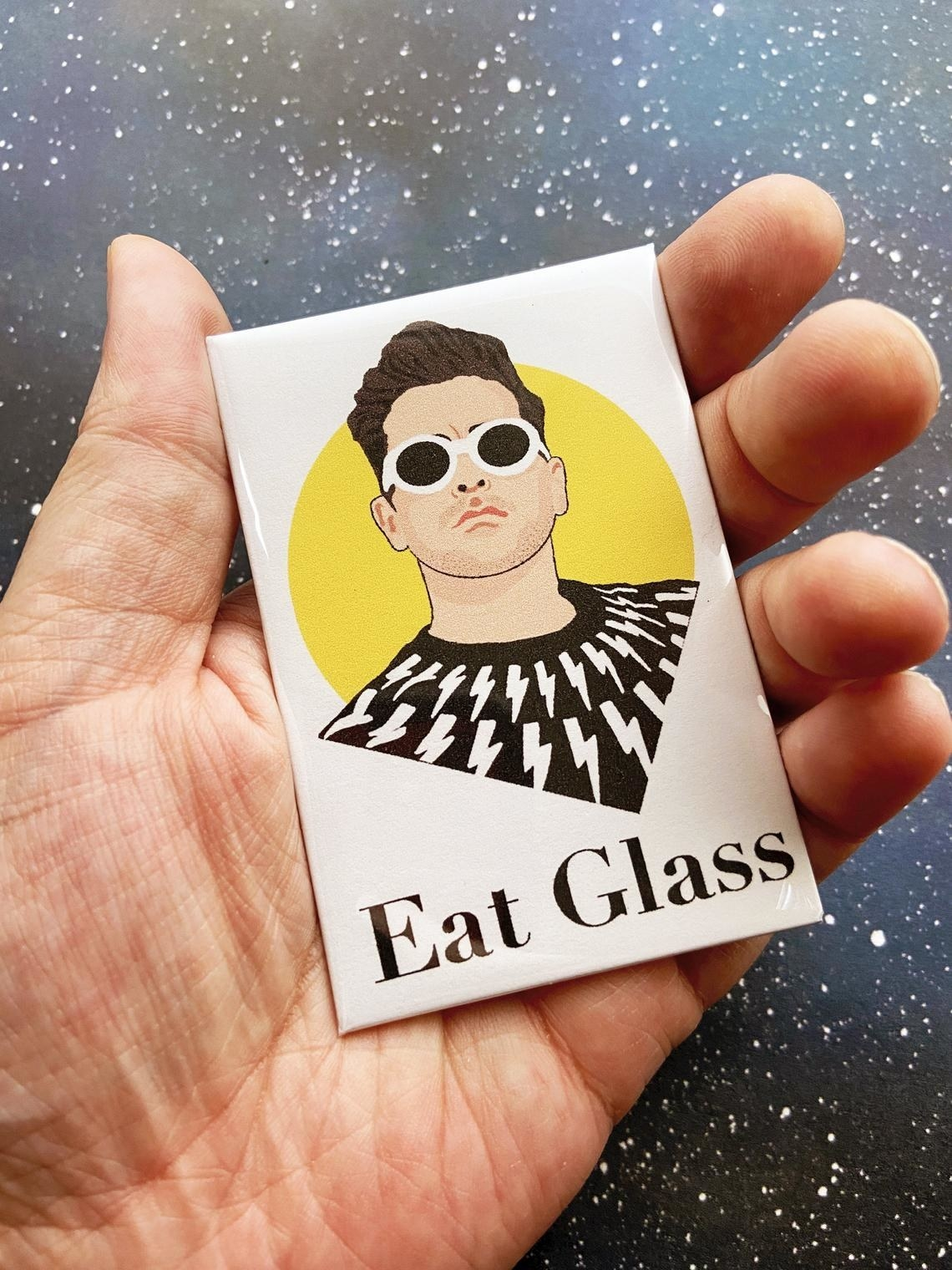 "A hand holding a rectangular magnet featuring a portrait of David and the words ""Eat glass"""